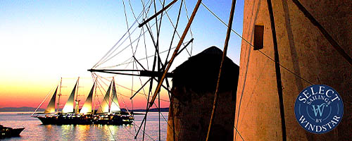 Sailing ships at sunset and windmills