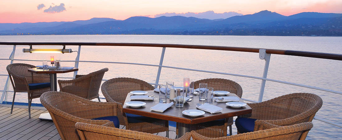 Tables set up for meals on the deck of a yacht at sunrise