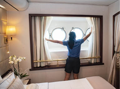Room attendant opening curtains in cabin